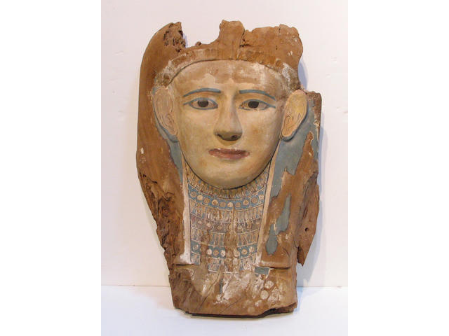 An Egyptian polychromed wood sarcophagus cover mask, (losses, painting refreshed)