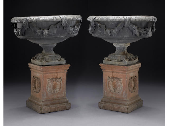 A pair of Continental Neoclassical lead garden urns on terracotta plinths, 18th century