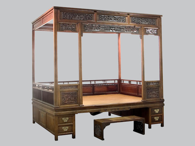 A carved mixed wood canopy bed, together with a foot stool