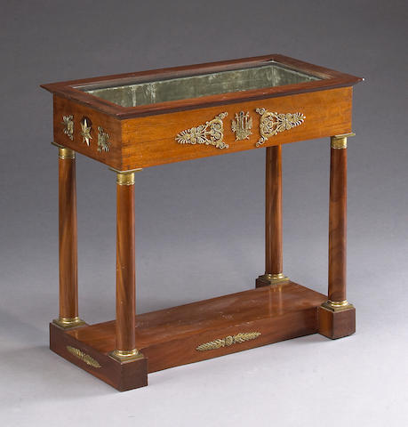 An Empire style gilt metal mounted mahogany vitrine table