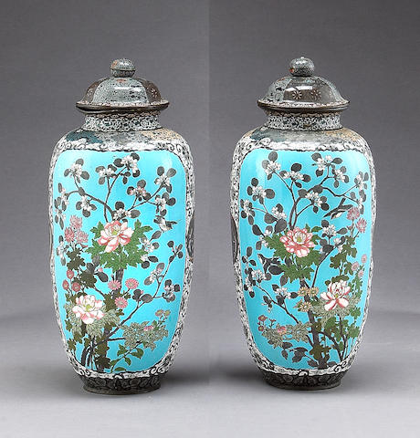 A pair of large cloisonne enameled metal covered vases with flowers and bird decoration, Meiji period (knobs reapinted and with losses to enamels, rima and cover slightly bent)