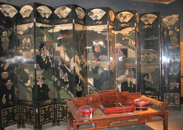A massive twelve panel black and polychrome lacquer coromandel screen