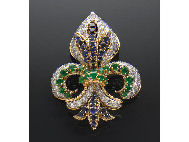 A diamond, sapphire, emerald and 18 karat white and yellow gold clip