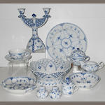 A Royal Copenhagen blue flower fluted partial dinner service including dinner ware, serving dishes, trivet, a pair of candlesticks, etc