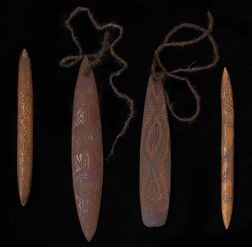 Four Australian Aborigine implements: two bull roarers, two message sticks