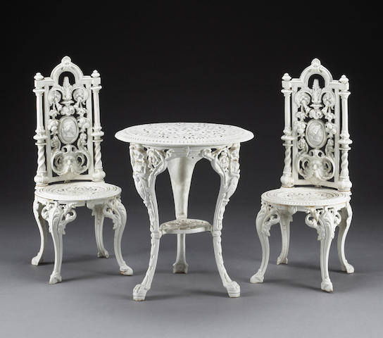 A Victorian cast iron garden table and pair of side chairs