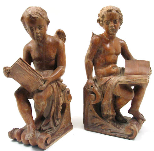 A pair of Italian carved walnut figures of cherubs