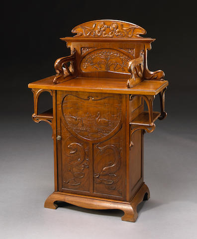 An Art Nouveau carved mixed wood cabinet