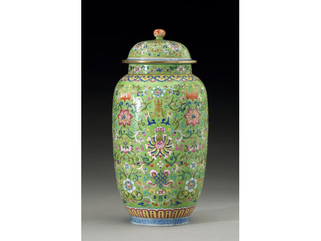 A green ground polychrome enameled covered jar with scrolling flowers