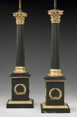 A pair of Empire style gilt and patinated bronze columnar lamps