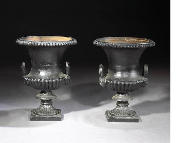 A pair of French Neoclassical style painted cast iron urns