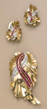 A retro diamond, ruby and eighteen karat gold brooch and pair of earrings,