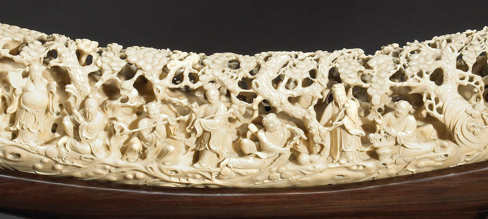 A massive carved ivory tusk decorated with Daoist and fictional characters