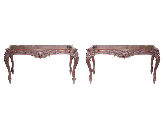 A pair of Louis XV style carved oak tables with carved aprons on cabriole supports