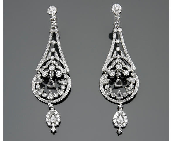 A pair of diamond and eighteen karat white gold pendant earrings