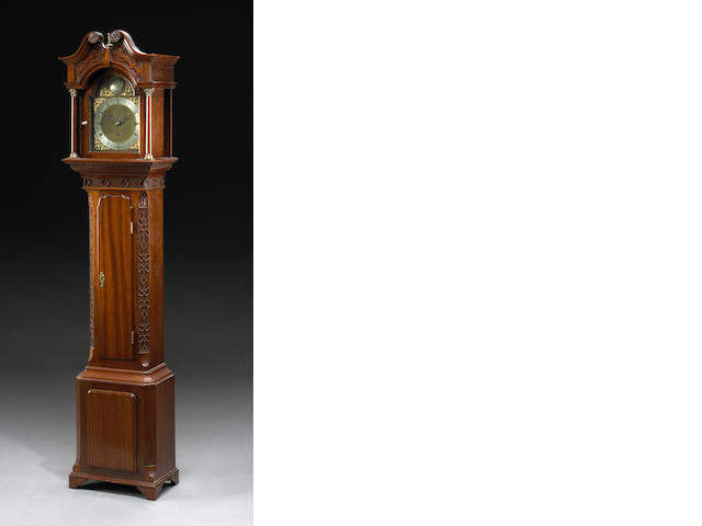 A George III style carved mahogany quarter chiming tall case clock
