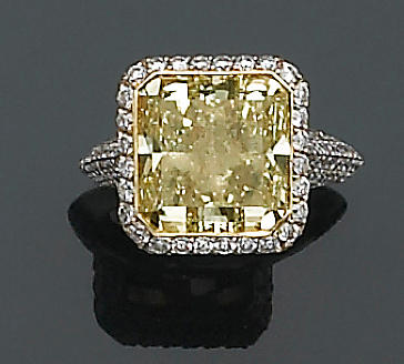 A natural fancy color diamond, diamond and eighteen karat white gold ring