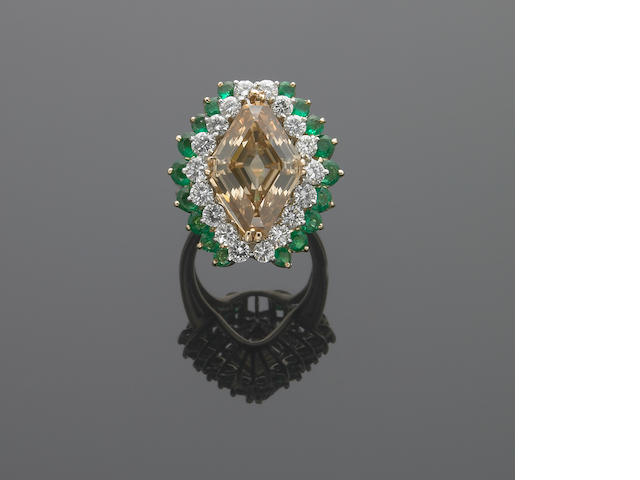 A fancy colored diamond, diamond, emerald and eighteen karat gold ring