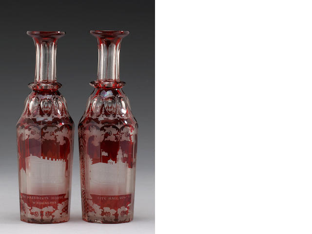 A pair of red glass bottles with the capitol pictured on front and back