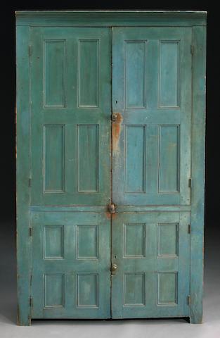 An American blue painted pine panel door corner cupboard