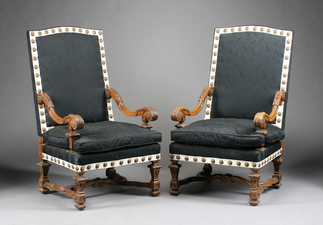 A pair of Louis XIV style carved walnut armchairs