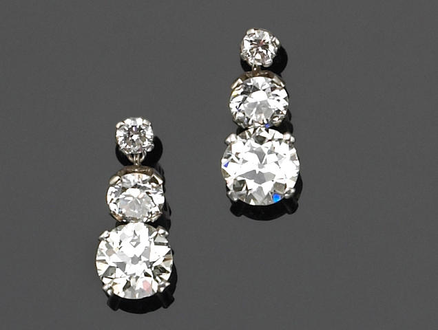 A pair of diamond and fourteen karat white gold earrings