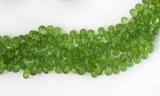 A peridot, diamond and fourteen karat white gold necklace