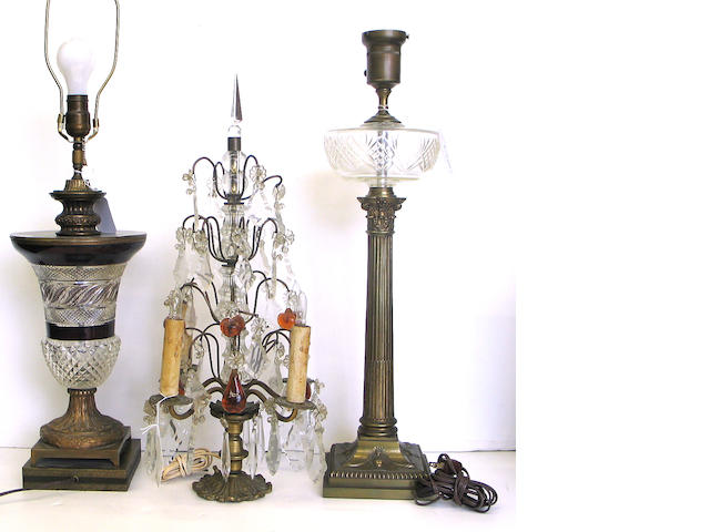 An assembled grouping of five brass and cut glass lamps or lighting fixtures