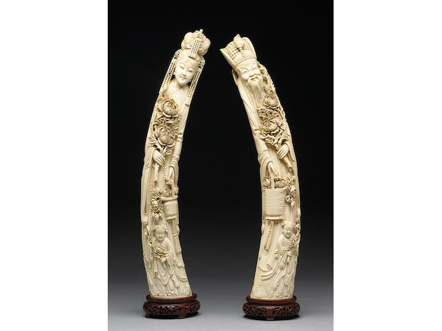 A near pair of tusk carvings depicting an emperor and empress holding peony sprays