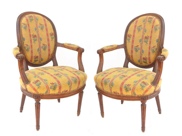 A pair of Louis XVI walnut and uphostered fauteuils