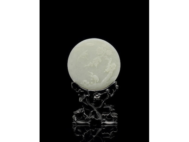 A finely carved white jade circular plaque Qianlong