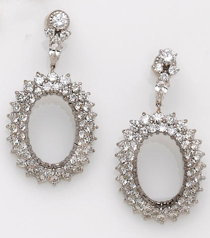 A pair of diamond and fourteen karat white gold earrings
