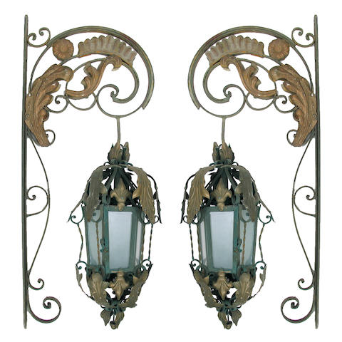 A pair of wrought iron hanging lanterns with wall brackets