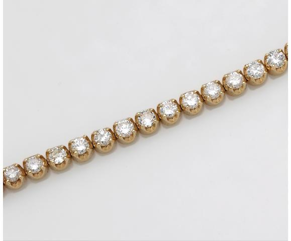 A diamond and fourteen karat gold line bracelet