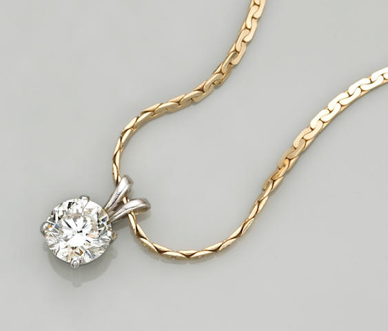 A diamond and fourteen karat white gold solitaire pendant with chain