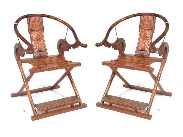 A pair of Chinese brass mounted hardwood horseshoe back armchairs