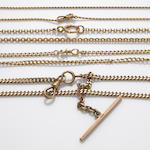 A collection of four 18k, 14k and 10k gold watch fobs and long chains