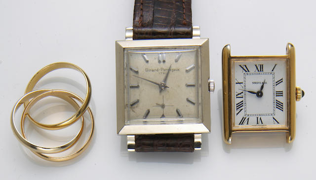 An 18k gold rolling ring together with two 14k gold wristwatches, Cartier, Girard-Perregaux, Shreve & Co.