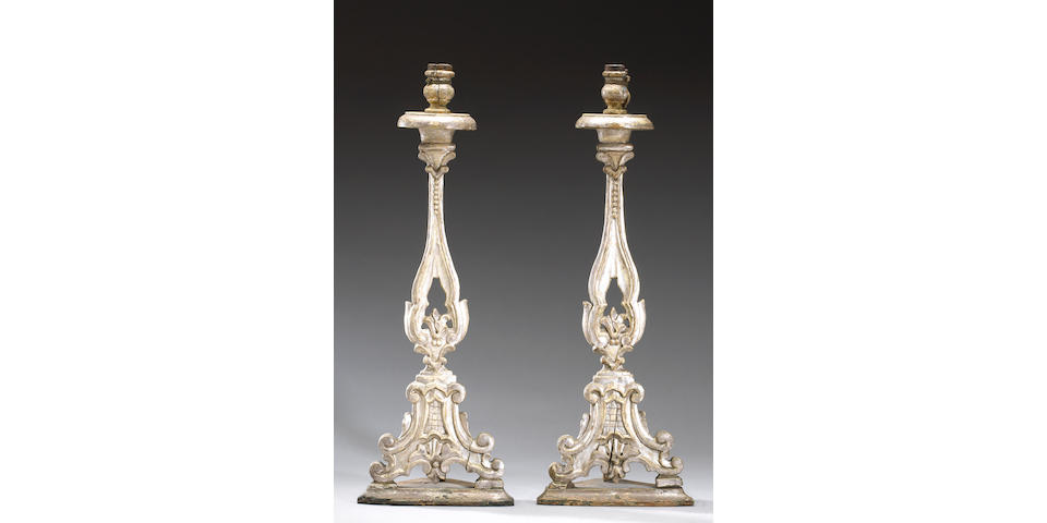 A pair of Italian silvered wood altar candlestick