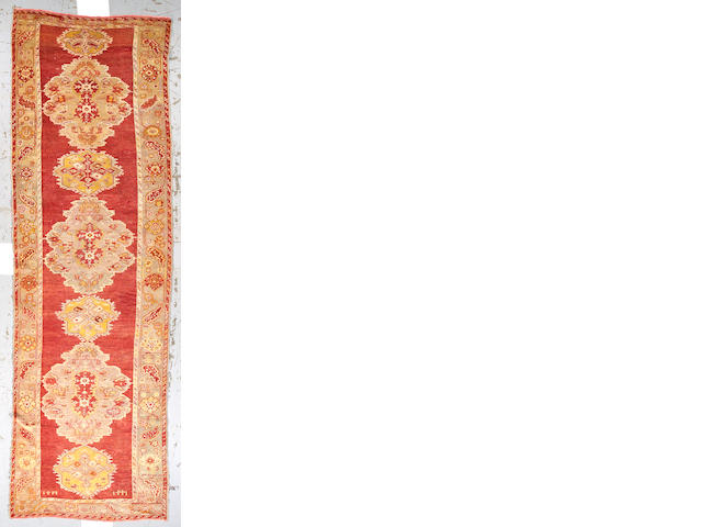 An Oushak runner West Anatolia, size approximately 4ft. 6in. x 14ft. 8in.