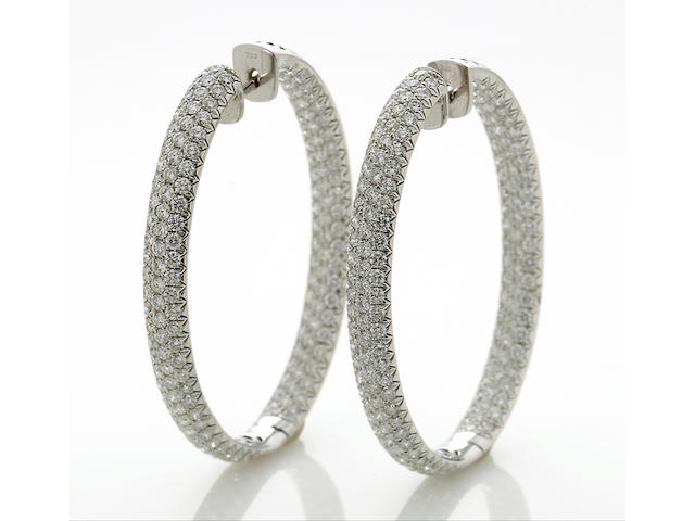 A pair of diamond oval-shaped hoop earrings