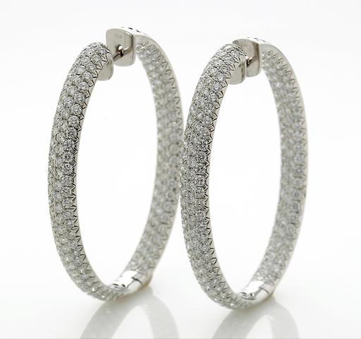 A pair of diamond oval-shaped hoop earrings