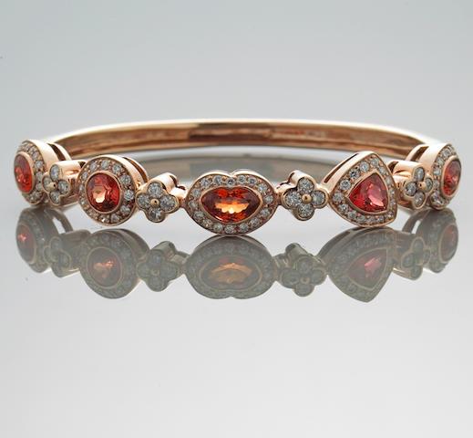 An orange stone and diamond bangle bracelet