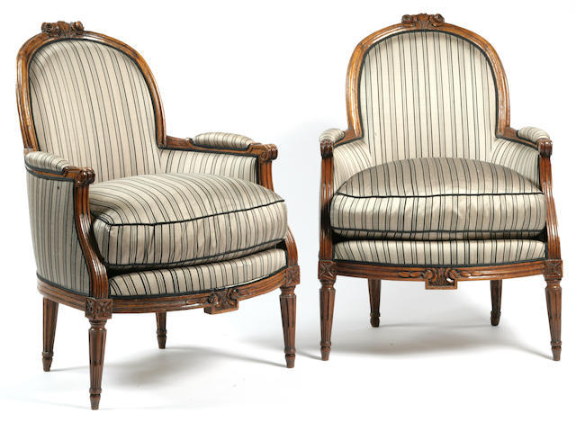 A pair of Louis XVI provincial style walnut bergères