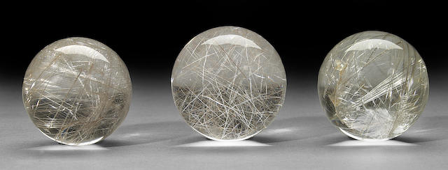 Group of three rutilated quartz spheres