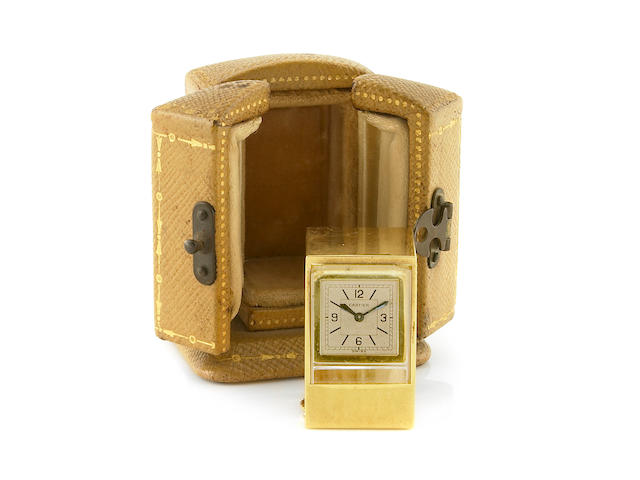 Cartier. A fine and rare miniature 18k gold keyless prism clock in fitted leather travelling case Circa 1960s