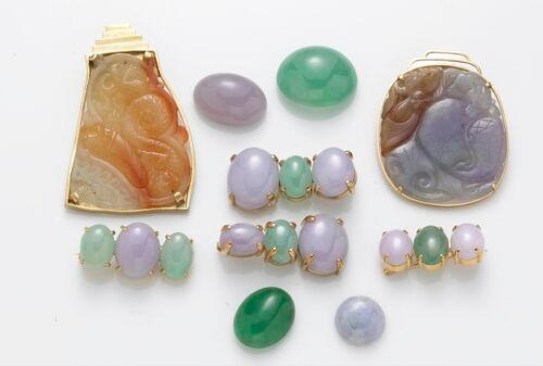 A collection of jade jewelry, including four loose jade pieces, a pair of matching lavander and green pendats, two green and lavander pins, two large carved jade pendants