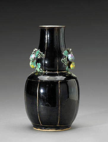 A mirror black porcelain vase of gourd shape with famille rose gourd vine handles and gilt trim