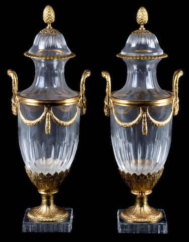 A pair of gilt bronze mounted glass covered urns