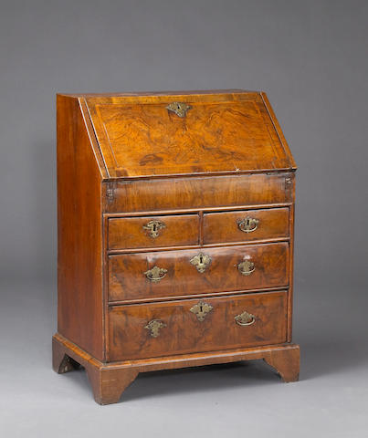 A diminutive George I walnut and feather banded slant front desk